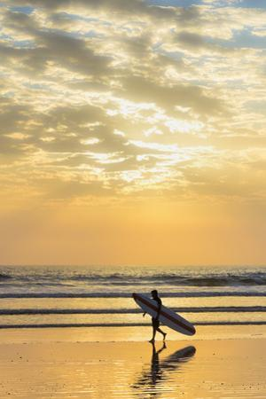 Surfer with Long Board at Sunset on Popular Playa Guiones Surf Beach