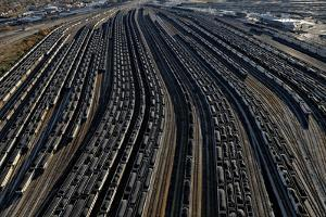 At a Coal Terminal, Railcars Loaded with Coal Line Up to Fill Waiting Ships by Robb Kendrick