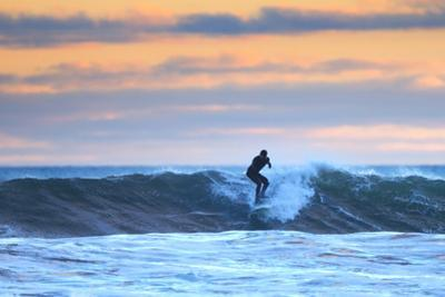 A Surfer Rides a Winter Wave Off the Coast of Maine at Sunset by Robbie George