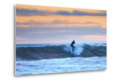 A Surfer Rides a Winter Wave Off the Coast of Maine at Sunset