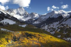 Sunlight on Golden Aspen Trees and Snow-covered Mountains by Robbie George