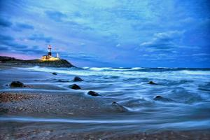 The Montauk Point Lighthouse Shining at Dusk by Robbie George