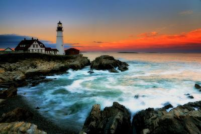 The Sun Setting Behind the Portland Head Light as Waves Surge onto the Rocky Shore