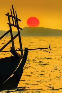 Big red setting sun beyond fishing boat moored off beach south of the city, Otres Beach, Cambodia by Robert Francis
