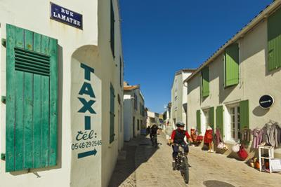 Cyclist on Rue Lamathe in the island's principal western town, Ars en Re, Ile de Re, Charente-Marit