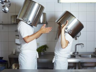 Two Chefs Having Discussion with Large Pans on their Heads by Robert Kneschke