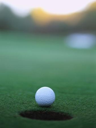 Golf Ball Close to Hole by Robert Llewellyn