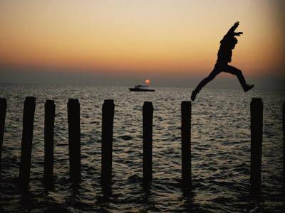 Bo Hoppin Leaps Between Pilings in the Chesapeake Bay off Great Fox Island, Virginia by Robert Madden