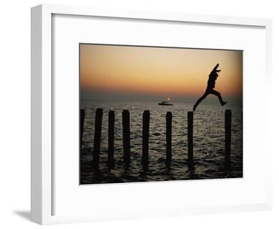 Bo Hoppin Leaps Between Pilings in the Chesapeake Bay off Great Fox Island, Virginia
