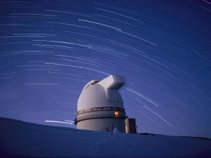 Time-Exposure of the Mauna Kea Observatory Taken at Night, the Streaks in the Sky are Star Trails by Robert Madden