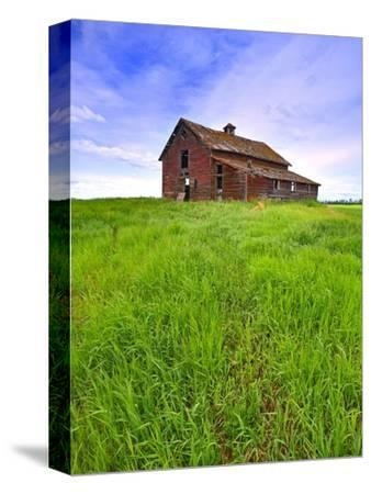 Abandoned red barn sitting on the top of a hill on a pioneer homestead in rural Alberta Canada