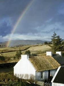 A Rainbow Arches over a Thatched White Cottage and Nearby Fields by Robert Sisson