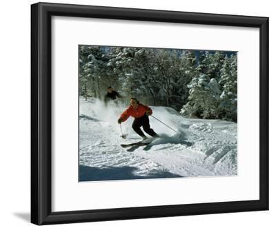 Skiers Heading Downhill Cut Through Powdery Snow
