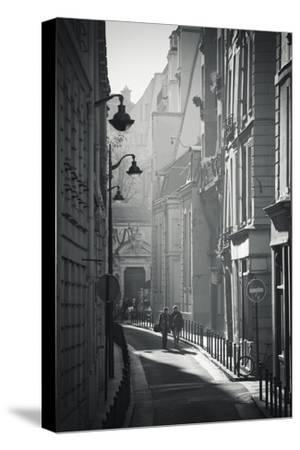 Two People Walking Up Sunny Side Street Near St Michel Notre Dame in Paris, France