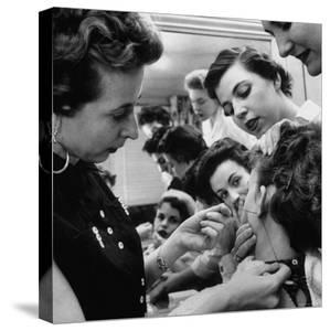 Woman Piercing Another Woman's Ears as Friends Look On by Robert W. Kelley