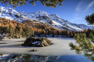 Autumn Reflections at Saoseo Lake Still Partially Frozen, Canton of Graubuenden, Switzerland by Roberto Moiola