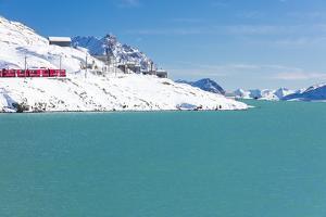 Bernina Express train in the snowy valley surrounded by Lake Bianco, Bernina Pass, Canton of Graubu by Roberto Moiola