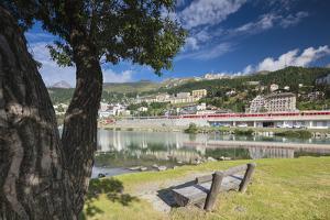 Bernina Express train runs past the village of St. Moritz surrounded by lake, Canton of Graubunden, by Roberto Moiola