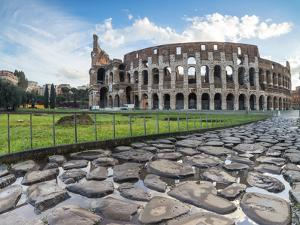 Blue sky at sunrise frames the ancient Colosseum (Flavian Amphitheatre), UNESCO World Heritage Site by Roberto Moiola