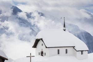 Clouds Above the Mountain Huts and Church Covered with Snow, Bettmeralp, District of Raron by Roberto Moiola