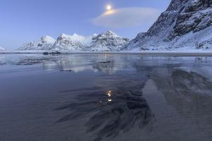 Full Moon Reflected in the Icy Sea around the Surreal Skagsanden Beach, Flakstad, Nordland County by Roberto Moiola