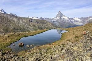 Hikers Admire the Matterhorn Reflected in Lake Stellisee, Swiss Alps by Roberto Moiola