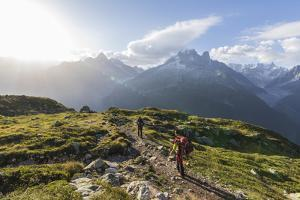 Hikers on the way to Lacs De Cheserys from Argentiere with Les Drus and Aiguille Verte in the backg by Roberto Moiola