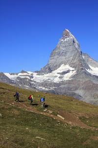 Hikers Proceed with the Matterhorn in Background in a Clear Summer Day, Switzerland by Roberto Moiola