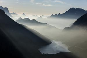 Mist on peaks of Dolomites and Monte Civetta seen from Cima Belvedere at dawn, Val di Fassa, Trenti by Roberto Moiola