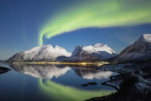 Northern lights and stars light up the snowy peaks reflected in sea, Bergsbotn, Senja, Norway by Roberto Moiola