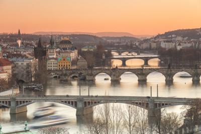 Orange sky at sunset on the historical bridges and buildings reflected on Vltava River, Prague, Cze by Roberto Moiola