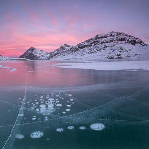 Panorama of ice bubbles and frozen surface of Lago Bianco at dawn, Bernina Pass, canton of Graubund by Roberto Moiola