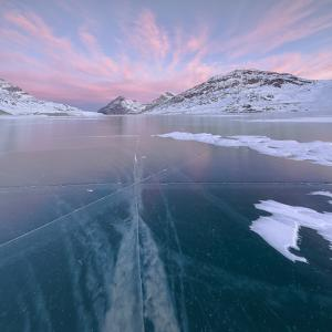 Panorama of the frozen Lago Bianco framed by pink clouds at dawn, Bernina Pass, canton of Graubunde by Roberto Moiola