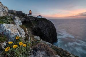 Pink sky at sunset and yellow flowers frame the lighthouse, Cabo De Sao Vicente, Sagres, Algarve, P by Roberto Moiola