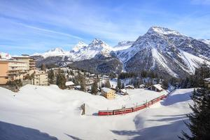 Red train of Rhaetian Railway passes in the snowy landscape of Arosa, district of Plessur, Canton o by Roberto Moiola