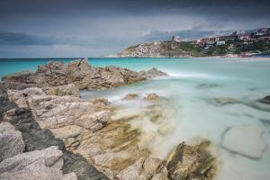 Storm clouds frame the village overlooking the turquoise sea, Santa Teresa di Gallura, Italy by Roberto Moiola