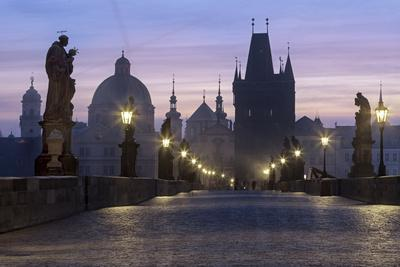 Street lanterns and old statues frame the historical buildings on Charles Bridge at dawn, UNESCO Wo