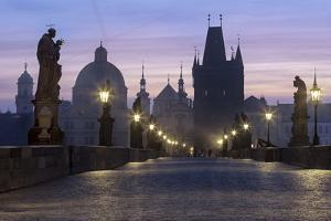 Street lanterns and old statues frame the historical buildings on Charles Bridge at dawn, UNESCO Wo by Roberto Moiola
