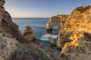 Sunrise on the Cliffs and Turquoise Water of the Ocean, Praia Da Marinha, Caramujeira by Roberto Moiola
