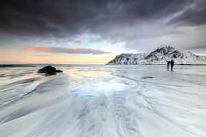 Sunset and Hikers on Skagsanden Beach Surrounded by Snow Covered Mountains by Roberto Moiola