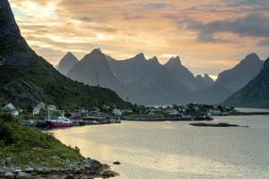 Sunset on the Fishing Village Surrounded by Rocky Peaks and Sea, Reine, Nordland County by Roberto Moiola