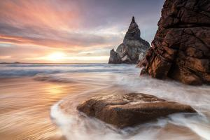 The Fiery Sky at Sunset Is Reflected on the Ocean Waves and Cliffs, Praia Da Ursa, Cabo Da Roca by Roberto Moiola