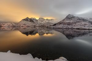 The Light of the Moon and Snowy Peaks Reflected in the Cold Sea Lit the Night at Svolvaer by Roberto Moiola