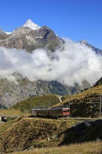 The Red Bahn Train Proceeds with the Peak of Dent Herens in the Background, Switzerland by Roberto Moiola