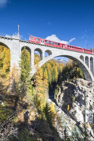 The red train on viaduct surrounded by colorful woods, Cinuos-Chel, Canton of Graubunden, Engadine,