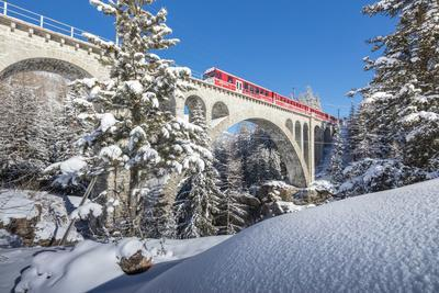 The red train on viaduct surrounded by snowy woods, Cinuos-Chel, Canton of Graubunden, Engadine, Sw