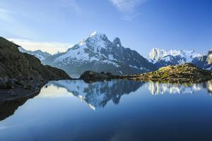 The Snowy Peaks of Mont Blanc are Reflected in the Blue Water of Lac Blanc at Dawn, France by Roberto Moiola