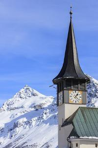 The typical alpine bell tower frames the snowy peaks, Langwies, district of Plessur, Canton of Grau by Roberto Moiola