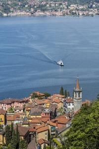 The typical village of Varenna surrounded by the blue water of Lake Como and gardens, Italy by Roberto Moiola