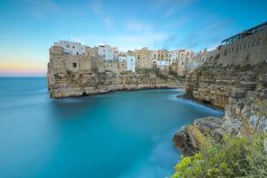 Turquoise sea at sunset framed by the old town perched on the rocks, Polignano a Mare, Province of  by Roberto Moiola